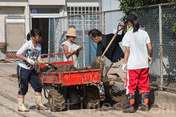 8月20日凌晨,日本廣島降暴雨,導致山崩,住宅區遭泥石流侵襲。居民們在清理泥土。(田震宇/大紀元)