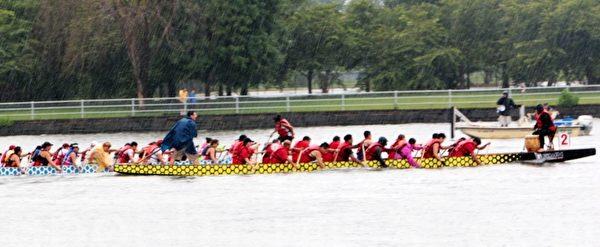 参赛选手在雨中湖面奋力划桨。(苏子清/大纪元)