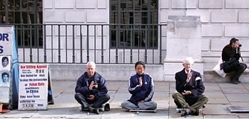 最早到伦敦中领馆前静坐抗暴的退休骨科医生罗伯特.吉布森(Robert Gibson)(左一),右一为他的老友瑟罗爵士。(新纪元)