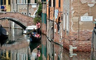 情侶乘貢朵拉浪漫遊威尼斯。(TIZIANA FABI/AFP)