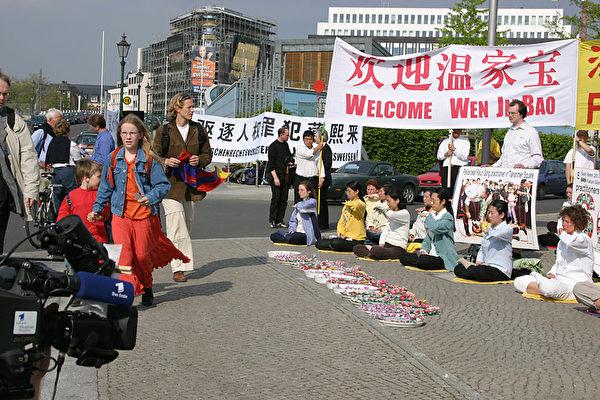 """2004年5月,薄熙来随温家宝一行访问欧洲五国,遭到人权团体抗议。法轮功在代表团抵达德国访问第一天的请愿活动中,打出了""""欢迎温家宝,法办江泽民,驱逐人权罪犯薄熙来""""等横幅。(大纪元资料图片)"""