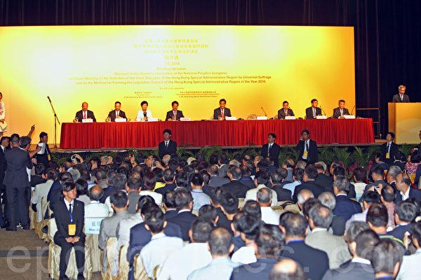 中共人大8月31日扼殺香港真普選,人大常委會副秘書長李飛9月1日在亞洲博覽館簡介人大決定,立法會議員梁國雄在李飛開始發言時起身抗議。(潘在殊/大紀元)