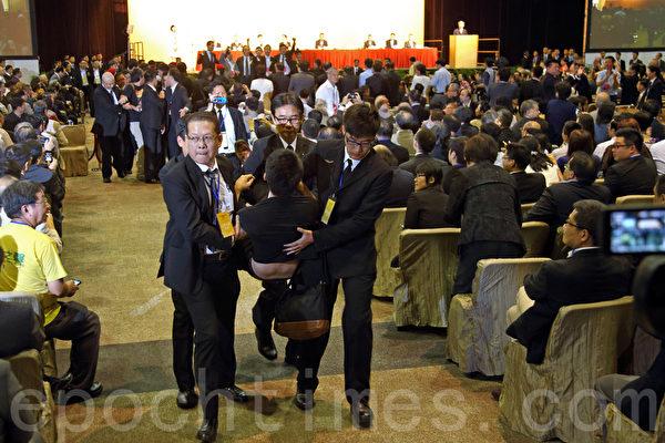 人大常委會副秘書長李飛9月1日在亞洲博覽館簡介人大的政改決定,場內外抗議聲不斷,泛民主派人士用離場來斥責中共背信棄義,否決香港民主,有抗議者被抬走。(潘在殊/大紀元)