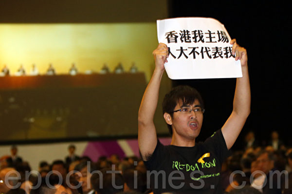 中共人大8月31日扼殺香港真普選,人大常委會副秘書長李飛9月1日在亞洲博覽館簡介人大決定,學聯的周永康離場抗議中共背信棄義,否決香港民主。(潘在殊/大紀元)