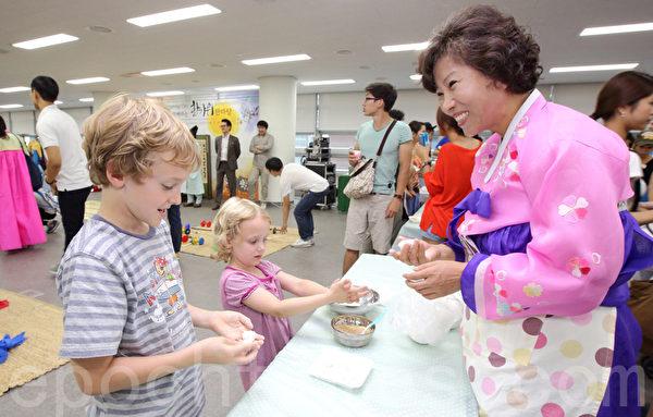 2014年9月2日,韓國首爾舉辦移居民中秋慶典,以韓國傳統的民俗慶典方式迎接中秋節。圖為做鬆餅。(全宇/大紀元)
