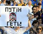 """8月28日,乌克兰南部的马里乌波尔市,一男子高举写有""""普京滚蛋!""""的标牌参加几千人呼吁乌克兰团结统一、要求俄罗斯撤军的大型集会。俄国军队的入境参战,进一步恶化了乌国东部危机。(ALEXANDER KHUDOTEPLY/AFP)"""