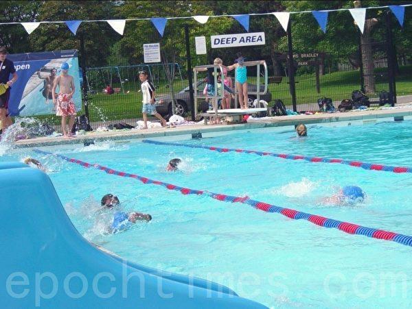 大孩子们游泳比赛开始了,孩子们依次跳入水中。(李文笛/大纪元)