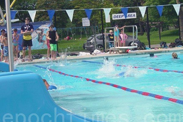 暑期游泳班上,左边是大班的孩子在教练的指导下练习游泳,右边小跳台上是小班的孩子在老师指导下练习跳水。(李文笛/大纪元)
