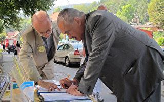 中、東歐經濟論壇會場外,前捷克共和國外交部長Karel Schwarzenberg簽名反對中共活摘器官罪行(明慧網)