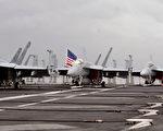 美國海軍於2014年9月13日聲明,經過一整天的搜救後,仍無卡爾‧文森號航空母艦上的大黃蜂戰機飛行員的下落,軍方決定停止搜索行動。圖為卡爾‧文森號航空母艦及數架停在艦上的F/A-18C大黃蜂艦載機。(AVANDERLEI ALMEIDA/AFP)