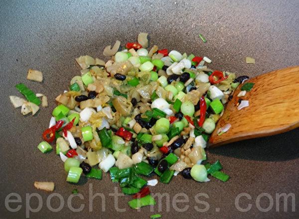 放入爆香过的豆豉、酸菜心拌炒提香。(林秀霞 / 大纪元)