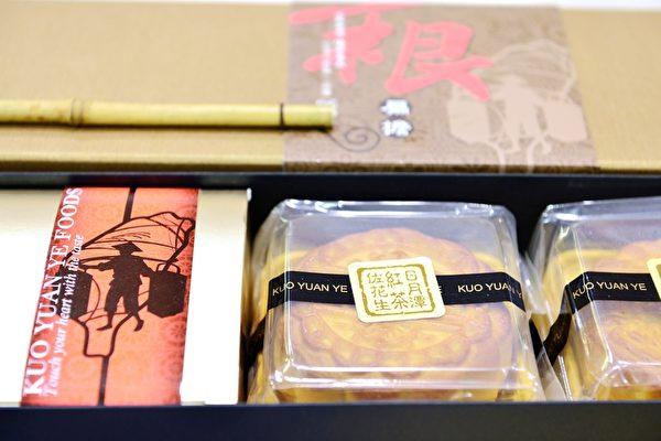"""形似扁担的长条礼盒里,摆放着四种口味的传统月饼,礼盒包装上还有一根迷你扁担,不负""""一根扁担""""之名。 (景浩/大纪元)"""