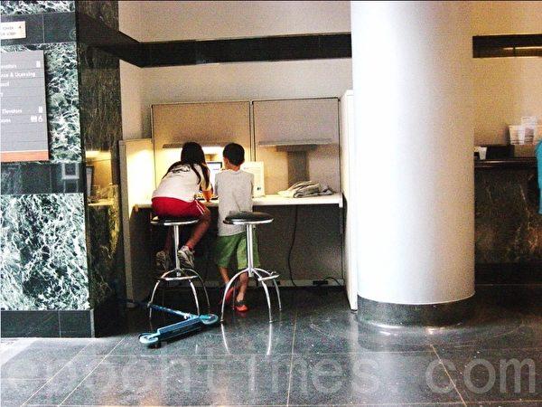 收费窗口的对面有台公用电脑,两位小朋友玩完了两轮车,又在玩电脑。电脑旁的大柱子后面有台取款机。 (李文笛/大纪元)