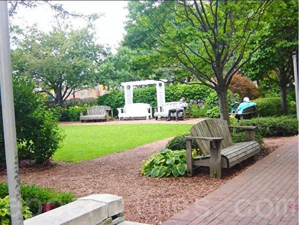 走廊的右边是花园,在花园的一角,有人在小酣,有人在读报。  (李文笛/大纪元)