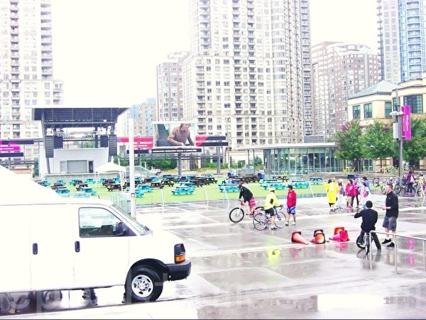 广场的右边是市图书馆,图书馆的后门有个玻璃房,供市民休息享用。 这是9月21日上午本市举办骑自行车活动,广场上也热闹起来。(李文笛/大纪元)