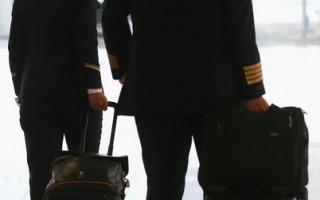 一名漢莎航空公司的飛行員(右)和一名機組乘務員走向機場大廳。當飛行員待遇優厚,而且不需要大學文憑。 (Alexander Hassenstein/Getty Images)