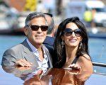 2014年9月27日,乔治·克鲁尼(左)与新婚妻子——伦敦人权律师阿拉姆丁在婚礼后乘坐快艇亮相。(ANDREAS SOLARO/AFP/Getty Images)