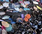 """2014年9月28日,香港民众以雨伞阻挡警方喷洒的胡椒与水柱。示威者因为使用雨伞和保鲜膜包裹等简易防御,被外界称为""""雨伞革命""""。(Alex Ogle/AFP/Getty Images)"""
