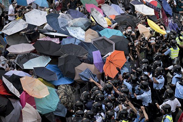 2014年9月28日,香港民眾以雨傘阻擋警方噴灑的胡椒與水柱。示威者因為使用雨傘和保鮮膜包裹等簡易防禦,被外界稱為「雨傘革命」。(Alex Ogle/AFP/Getty Images)
