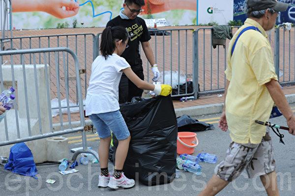 金钟集会现场秩序井然,更有不少市民主动清理垃圾,维持街道整洁。(孙青天/大纪元)