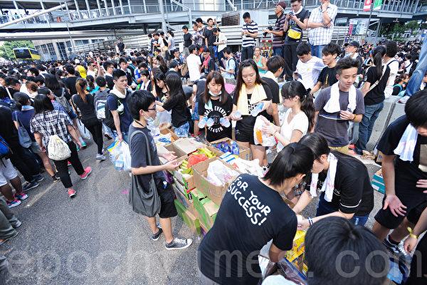 和平占中运动踏入第二天,香港政府总部一带的金钟有继续有大批市民集会。烈日下静坐十分辛苦,但市民守望相助,互相传递物资,又帮助扶持有需要的人,现场洋溢温情。(孙青天/大纪元)