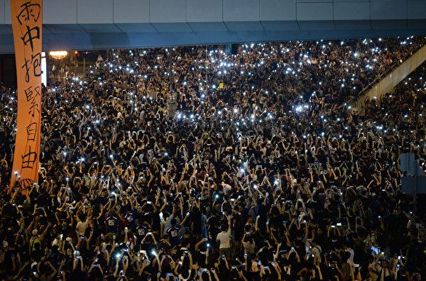 9月29日晚間,包括金鐘、中環、灣仔、銅鑼灣和旺角,5處鬧區聚集爆滿群眾並揮舞手機讓藍光亮成一片燈海。(DALE DE LA REY/AFP)