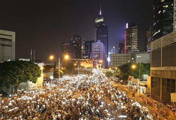 9月29日晚間,包括金鐘、中環、灣仔、銅鑼灣和旺角,5處鬧區聚集爆滿群眾並揮舞手機讓藍光亮成一片燈海。(AARON TAM/AFP)