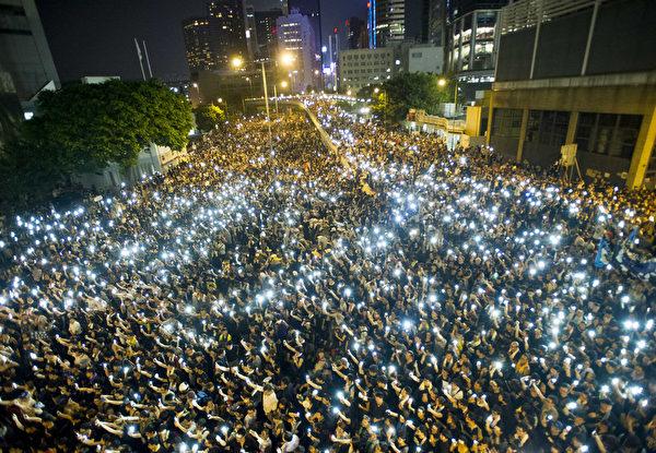 9月29日晚間,包括金鐘、中環、灣仔、銅鑼灣和旺角,5處鬧區聚集爆滿群眾並揮舞手機讓藍光亮成一片燈海。(XAUME OLLEROS/AFP)