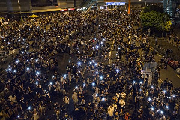 9月29日晚間,包括金鐘、中環、灣仔、銅鑼灣和旺角,5處鬧區聚集爆滿群眾並揮舞手機讓藍光亮成一片燈海。(Paula Bronstein/Getty Images)