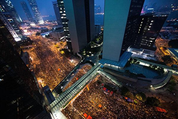 香港「太陽傘運動」進入第三天,繼續有數以萬計市民晚上在商業區金鐘集會。儘管曾一度下起大雨,集會者仍然留守,堅持爭取梁振英下台、人大道歉。(Anthony Kwan/Getty Images)