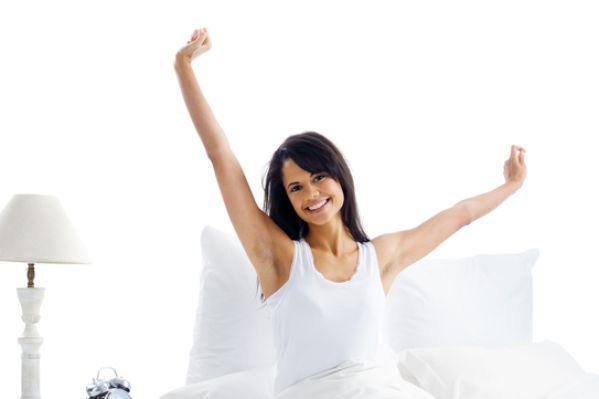 累了,困了的女人起床和打哈欠与伸展,坐在床上(图片来源:Fotolia)