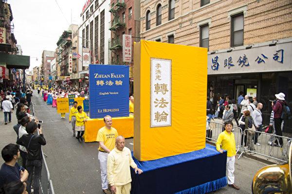 2013年5月18日,紐約曼哈頓,來自世界各地的法輪功學員在此舉行慶祝法輪大法弘傳21週年大遊行。圖為遊行的第一主題「大法洪傳」方陣。圖為《轉法輪》大型書模型。(戴兵/大紀元)