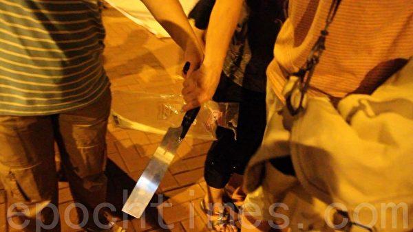 2013年7月4日晚,青关会成员在落马洲出动锯刀,涉嫌恐吓在场的法轮功学员和采访记者,但现场的警察却以没有人受伤为由,只是登记在案,不作任何处理。(大纪元)