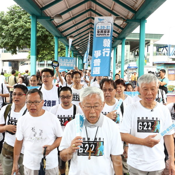 香港30多個民間團體發起連續七日的「毅行爭普選」活動,最後一日6月20日一早從中環七號碼頭出發,途經國際金融中心,約十點抵達中聯辦。(蔡雯文/大紀元)