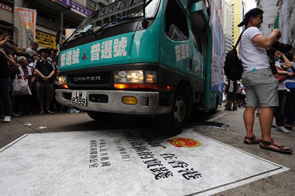 香港民間人權陣線發起的「七·一」大遊行,7月1日下午3時半前正式由銅鑼灣維多利亞公園起步,遊行隊伍中民眾以各式展板表達訴求。圖為民眾以車子輾過白皮書表達抗議之意。(文瀚林/大紀元)