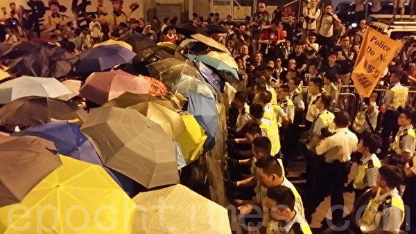 27日凌晨3时后,数十名配戴头盔及盾牌的防暴警察操向添美道,并用警棍驱赶示威者及喷射胡椒喷雾,情况混乱。其后一批军装警员与防暴警察交换位置,期间有示威者用雨伞与警员推撞,有警员强行扯走雨伞。(宋祥龙/大纪元)