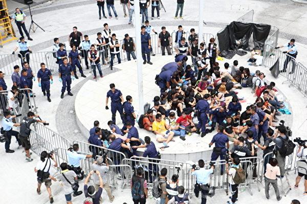 學聯兩位學生領袖周永康、岑敖暉在內的數十名學生,通宵堅守政總公民廣場旗杆下的位置,警方27日中午過後開始清場,逐一把他們帶走或抬走。期間學生沒有作出反抗。(蔡雯文/大紀元)