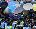 2014年9月28日,民众以雨伞阻挡警方喷洒的胡椒与水柱。(aaron tam/AFP/Getty Images)