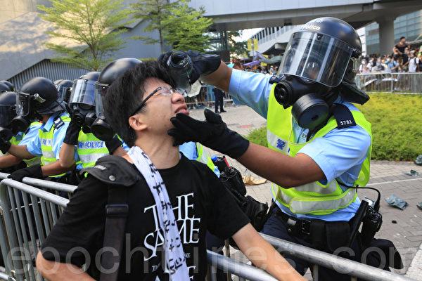 """29日下午,香港政府总部前的金钟夏悫道,这位最简单的防护装置都没有的年轻人,对向他喷射胡椒喷雾的防暴警察怒吼,""""为什么你要对我们这些手无寸铁的市民下手?""""戴上防毒面具的防暴警察、虽然看不到面孔和表情,用手轻拍愤怒的示威者,连声说""""知道,知道"""",转身拿出自己的水壶,为这位他刚刚出手伤害的市民冲洗眼睛。(余钢/大纪元)"""