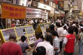 图为香港旺角街头的真相点,令人震撼的迫害酷刑图片,吸引民众停下脚步围观。(摄影:李明/大纪元)