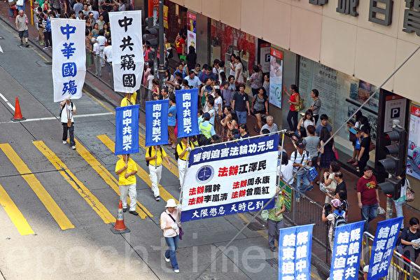 香港法轮功学员10月1日举行国殇日游行,8百多人的游行队伍途径多个闹市区,吸引不少市民驻足观看,有参与太阳伞学运的大学生高喊法轮大法好,也有大陆游客表示支持法轮功学员的信仰。(潘在殊/大纪元)