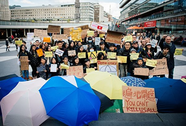 """2014年10月1日,瑞典首都斯德哥尔摩的声援者手持标语支持香港的""""雨伞革命""""。  (JONATHAN NACKSTRAND/AFP/Getty Images)"""