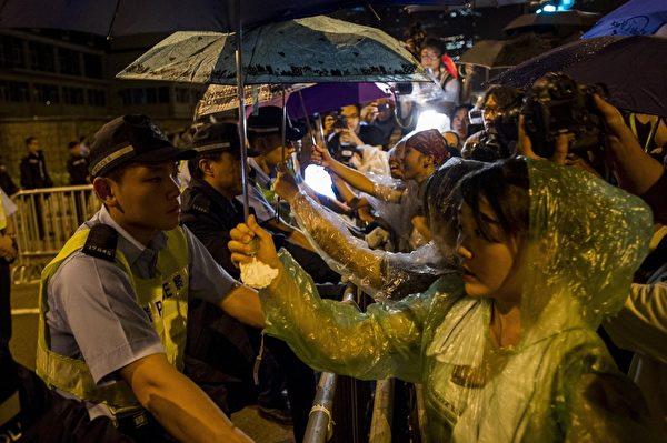 2014年10月2日,香港,参与活动的学生把伞举到了虎视眈眈的警察的头上,为他们遮雨。 (XAUME OLLEROS/AFP/Getty Images)
