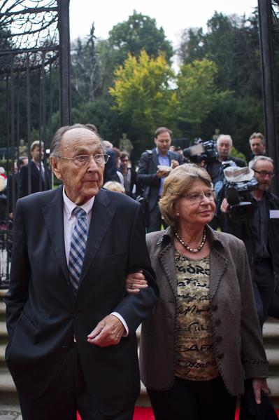 2014年9月30日,紀念數以千計的東德難民通過西德駐布拉格使館奔向西方自由世界25週年。圖為德國前外長漢斯-迪特里希‧根舍(左)和他的妻子走進使館花園。(Matej Divizna/Getty Images)