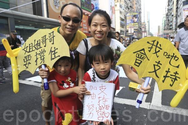 「雨傘革命」的參與者,要求梁振英下台,爭取真普選。圖為10月2日,香港市民全家來為學生打氣。(余鋼/大紀元)