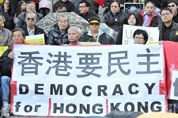 2014年10月1日晚,数百名卡尔加里市民在奥林匹克广场举行集会,支持香港太阳伞革命。图为卡城民主促进会成员打出香港要民主的标语。(吴伟林/大纪元)
