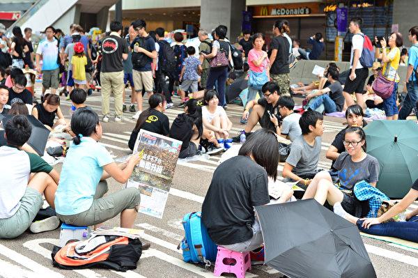 """抗议的香港学生们提出的口号是""""罢课不罢学"""",他们现在一边罢课要求民主改革,一边在街上做功课。(大纪元)"""