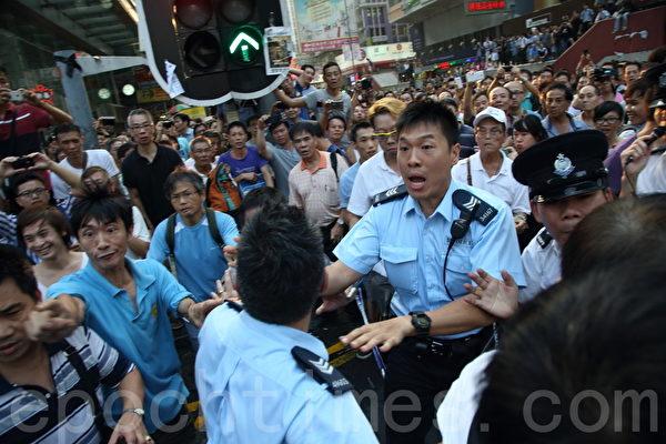 中共黑社會黑幫成員冒充市民身份,恐嚇、辱罵和襲擊參與雨傘革命集會的市民,現場警力單薄,警員試圖阻擋鬧事者。(潘在殊/大紀元)