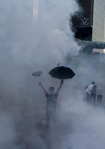 香港民主黨創黨主席李柱銘所寫的一篇名為《誰將與香港同在?》的投稿心聲,疾呼美英執行與北京簽署的香港條款。圖為2014年9月28日香港,爭民主民眾受到鎮暴警察的催淚瓦斯攻擊。(XAUME OLLEROS/AFP)