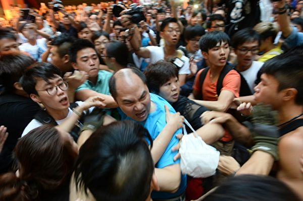 """2014年10月4日,中共控制的黑帮成员与外围组织以""""反占中""""的名义,在旺角的""""雨伞革命""""和平集会地点挑衅,想引起骚乱,制造清场的借口。(宋祥龙/大纪元)"""